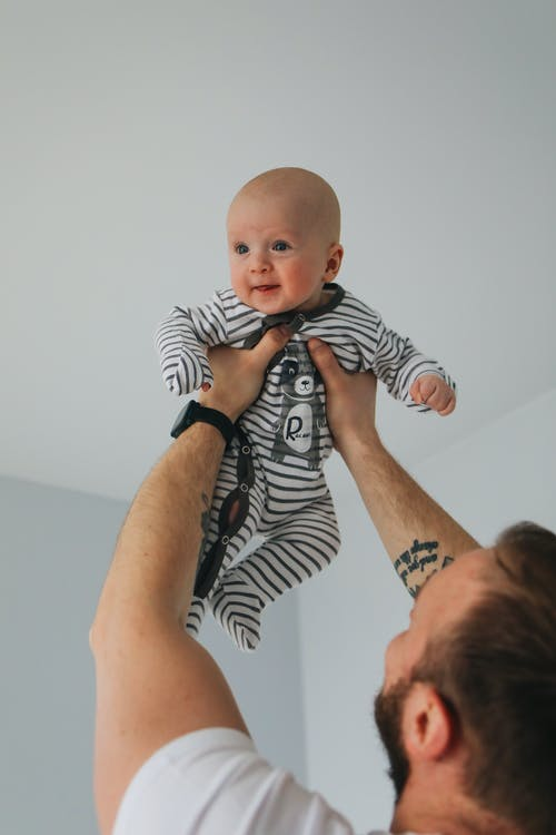 Man in White T-Shirt Carrying Baby in Black and White Stripe Onesie