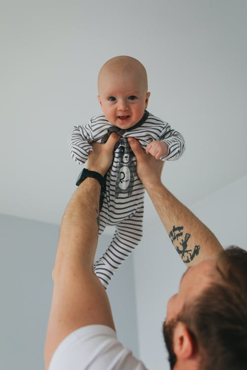 Man Carrying Baby in Black and White Stripe Onesie