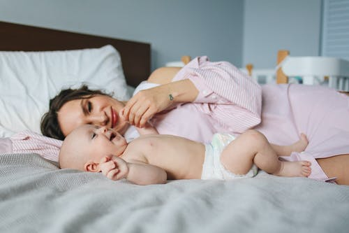 Woman in Pink Dress Lying on Bed Next to Baby in Diapers