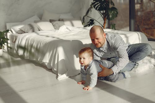 Happy father with toddler in bedroom