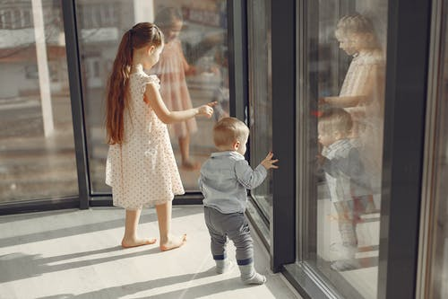 Cheerful brother and sister standing near window