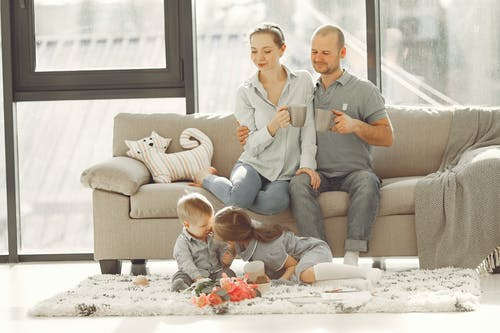 Parents drink tea while sitting with children in living room