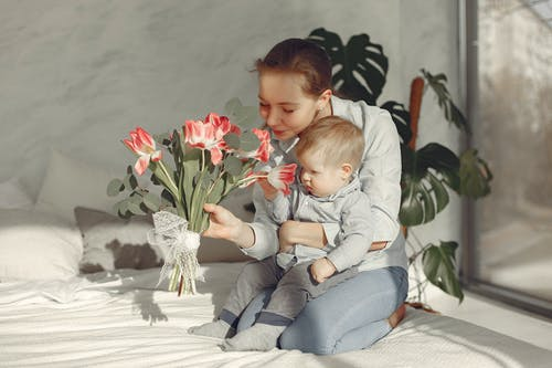 Happy mother and toddler in bedroom