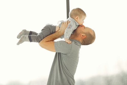 Man in Gray Short Sleeve T-shirt Carrying Baby