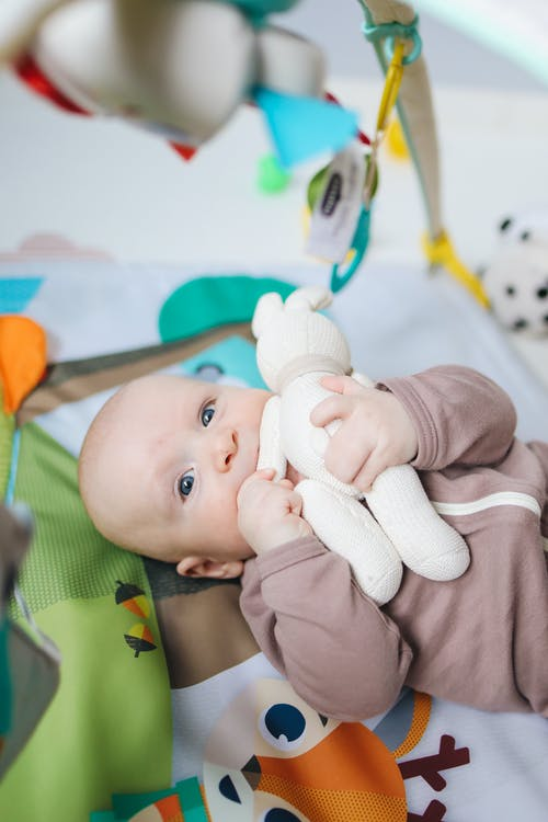 Baby in Onesie Lying on Green and Blue Mat