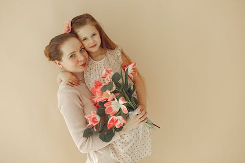 Happy mother with daughter and flowers