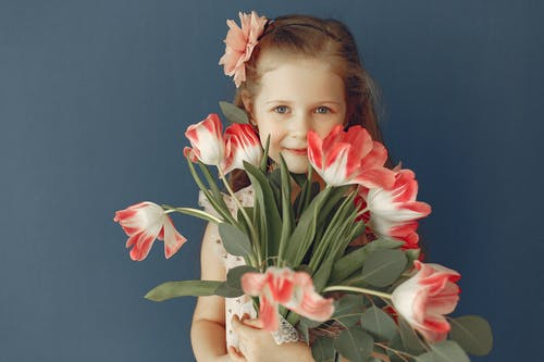 Girl Holding Pink and White Flowers Smiling