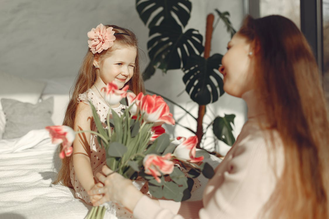 Mother Showing  White and Red Flowers To Her Baby