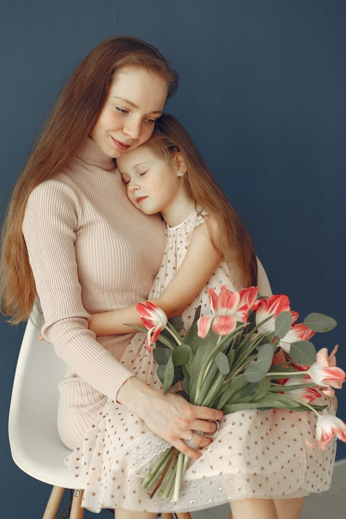 Tender little girl embracing mother with flowers