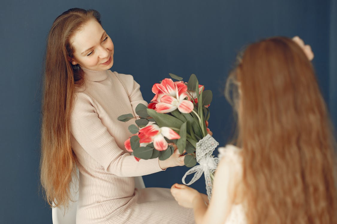 Happy daughter giving flowers to mother