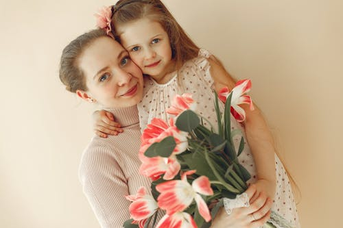Woman In Knit Sweater Holding Girl In White Floral Dress