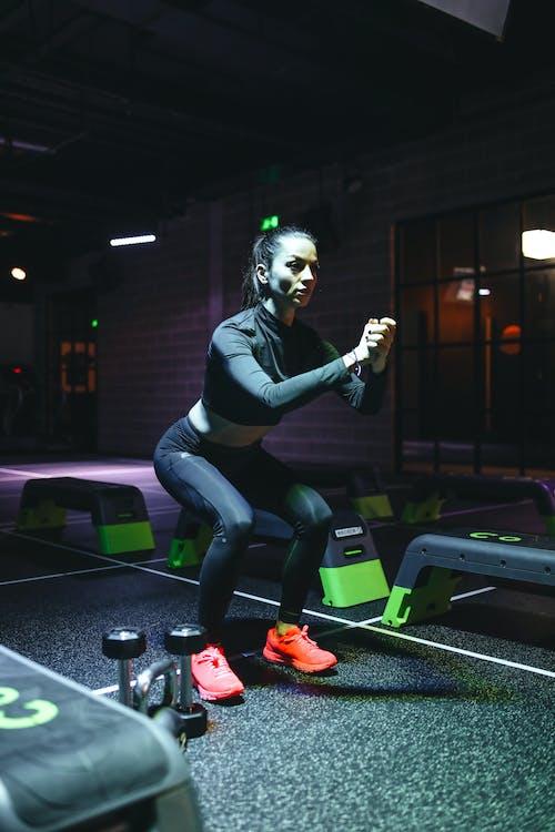 Woman In Black Long Sleeve Shirt And Black Leggings Doing Squats