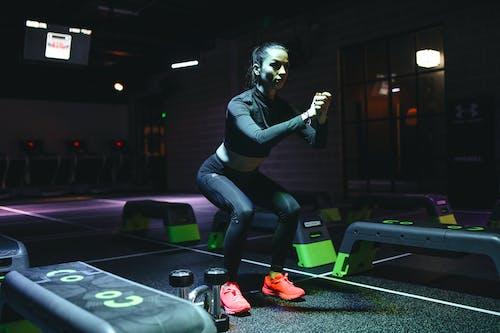 Woman in Black Long Sleeve Top and Black Leggings Doing Yoga