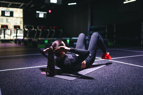 Woman in Black Leather Top and Black Leggings Lying on Mat Doing Yoga
