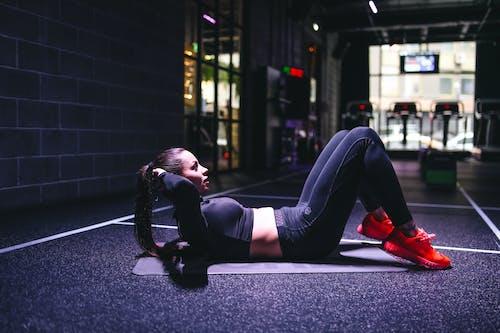 Woman in Black Leggings Lying on A Mat