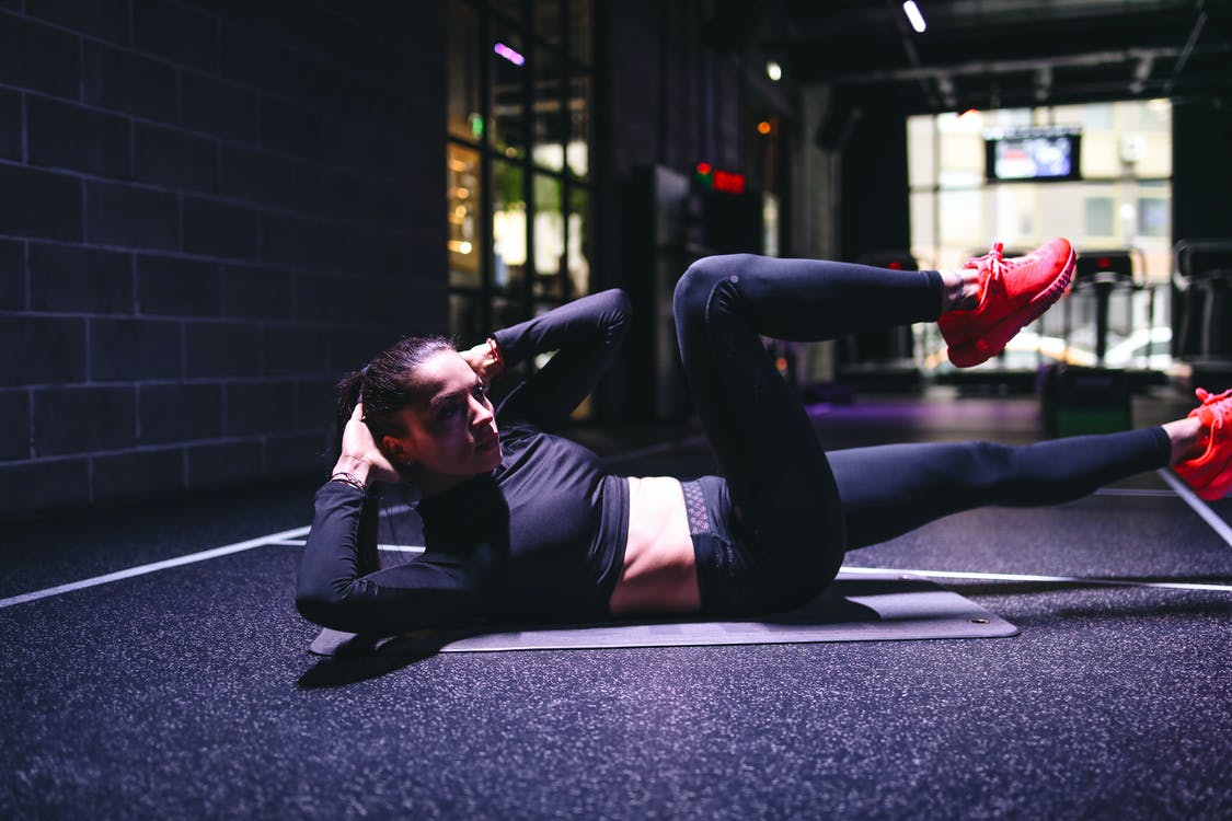 Strong sportswoman doing criss cross exercise on mat