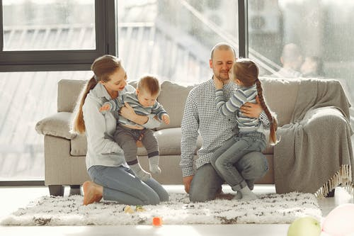 Cheerful parents playing with kids in living room