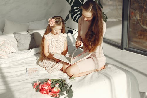 Woman Sitting On A Bed With Her Daughter