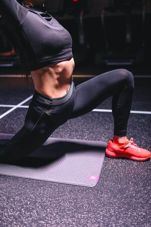 Sporty woman doing lunge exercise in gym