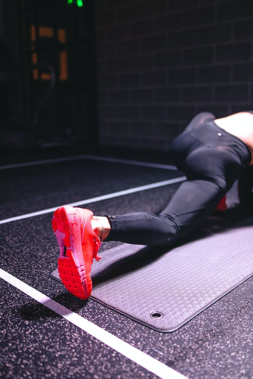 Woman in Black Leggings and Red Shoes Doing Exercises In The Gym