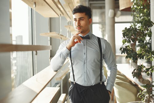 Pensive handsome ethnic male in elegant suit and bow tie standing in modern cafe with hand in pocket and looking through window