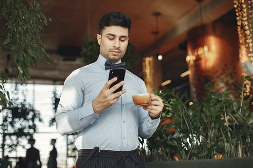 Man In Dress Shirt Holding Black Smartphone