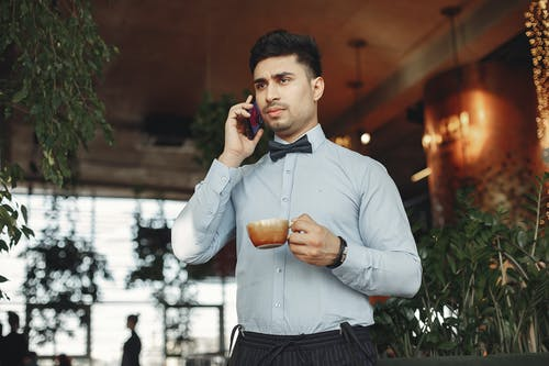 Busy handsome ethnic man in formal suit and bow tie standing in lobby of modern cafe with cup of hot coffee in hand and answering phone call while looking away