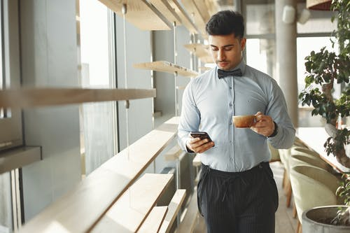 Man In Blue Dress Shirt And Black Dress Pants Holding Smartphone