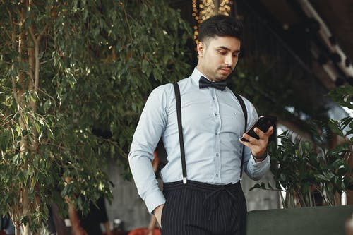 Man In Dress Shirt And Black Dress Pants Holding Black Smartphone