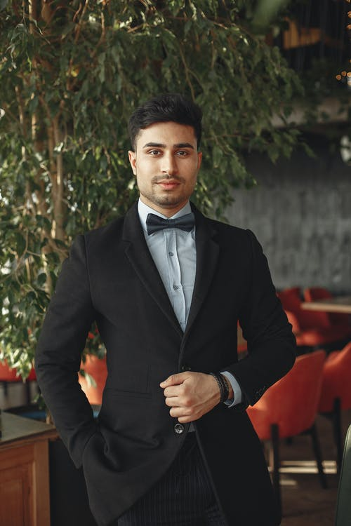 Man In Black Suit Standing Near Green Plant