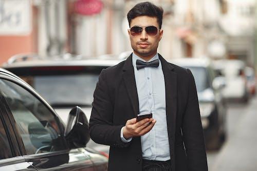 Man In Black Suit Jacket Holding Smartphone
