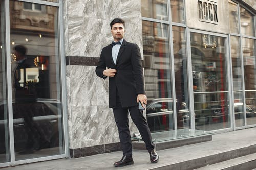 Man in Black Suit Standing Near Glass Door