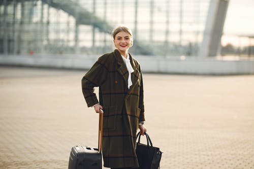Positive smiling young female traveler in casual warm coat with suitcase and ladies bag standing near airport terminal and looking at camera