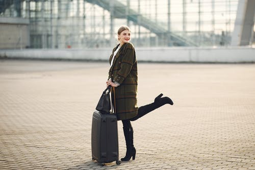 Full body of stylish female tourist in warm clothes and high heeled boots standing on background of blurred airport terminal with luggage and ladies bag