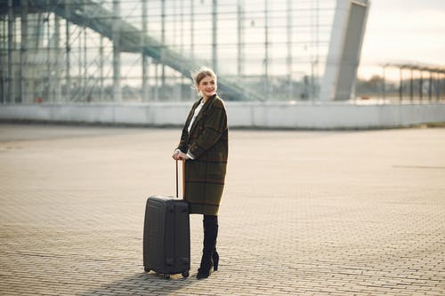 Cheerful female tourist with suitcase