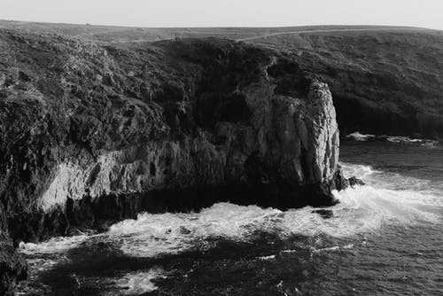 Black and white amazing aerial view of rocky coastline and foamy sea waves rolling to rocky cliff on daytime