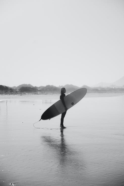 Gray-scale Photo of Man Holding Surfboard Standing on Beach