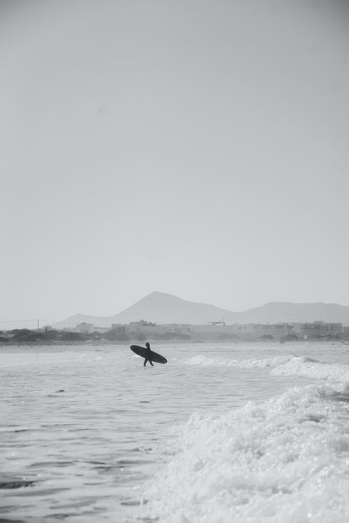 Grayscale Photo of Person Carrying Surfboard Walking on Water
