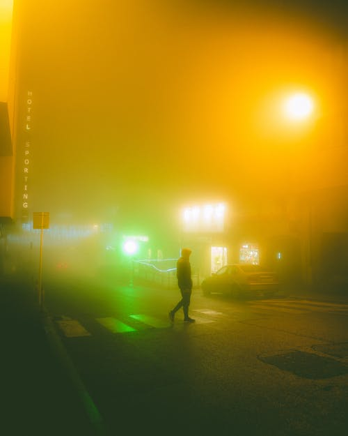 Unrecognizable person walking on illuminated street in evening