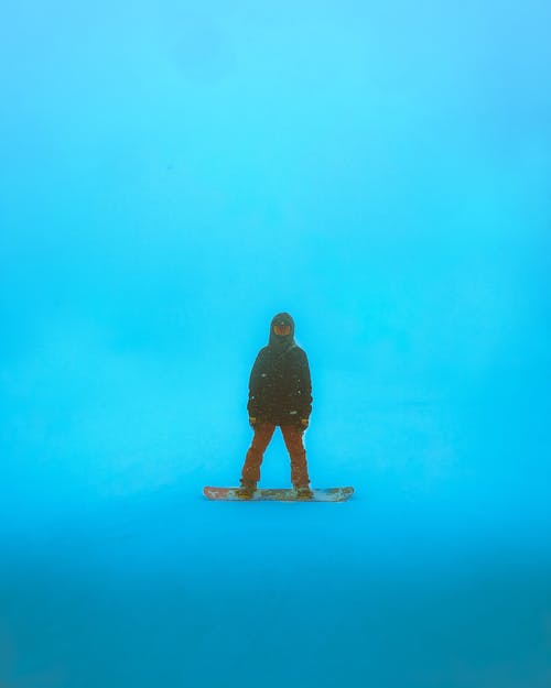 Unrecognizable person standing on snowboard on blue background