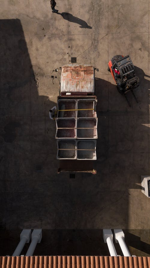 Aerial view of shabby truck with empty boxes parked in loading area with forklift and people nearby