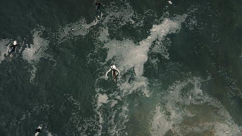 Aerial view of surfers in springsuits rowing surfboards in foamy water waves in ocean