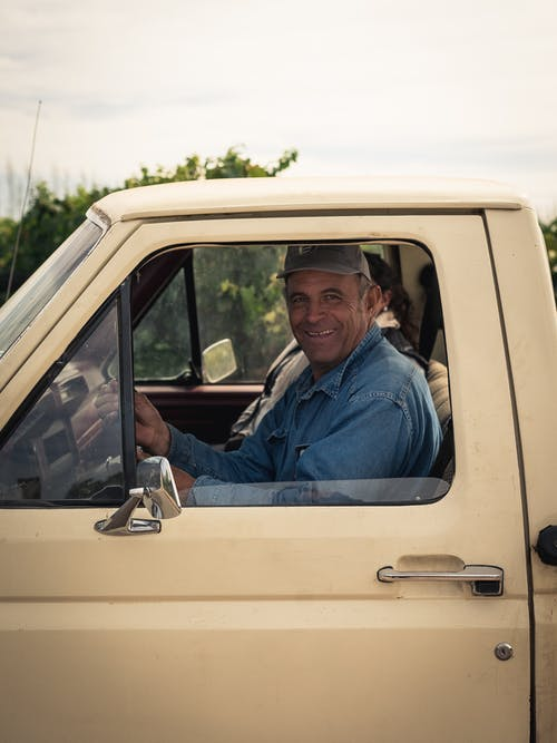 Man In Blue Denim Top Sitting Inside A Vehicle