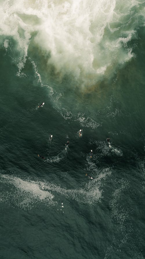 Aerial View Of People Surfing On Sea Waves