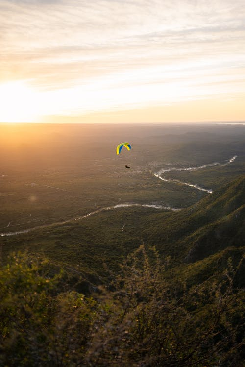 Paraglider soaring high above green terrain in sunset