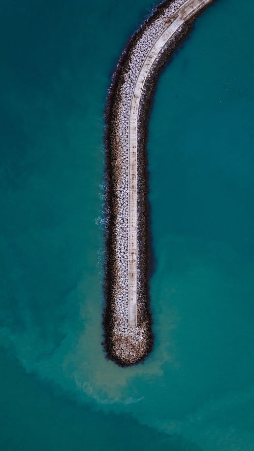 Aerial top view of breakwater with pier in clear turquoise water of ocean lagoon