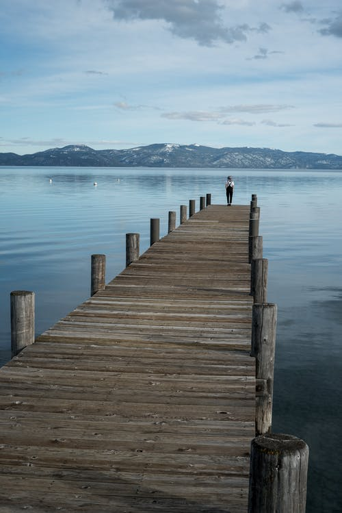 Distant traveler standing in solitude on long wooden pier with landscape of calm lake in highlands