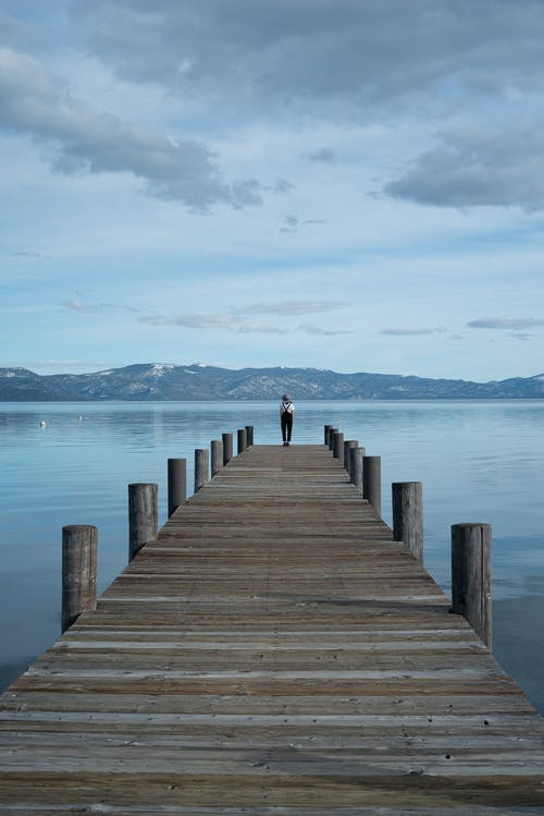 Person, Die Auf Brown Wooden Dock Auf See Steht