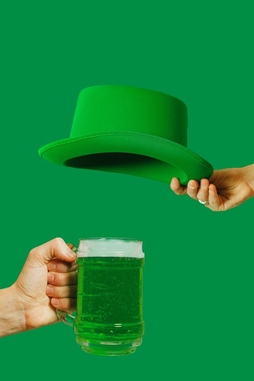 Person Holding Green Hat and Glass