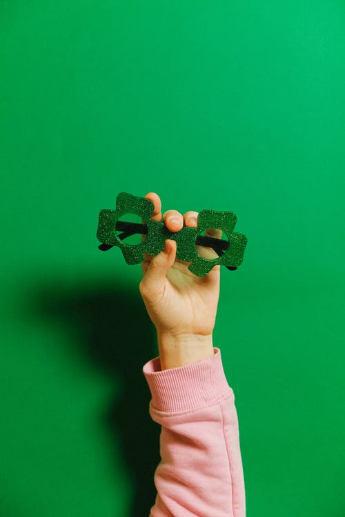 Person Holding Green Glasses